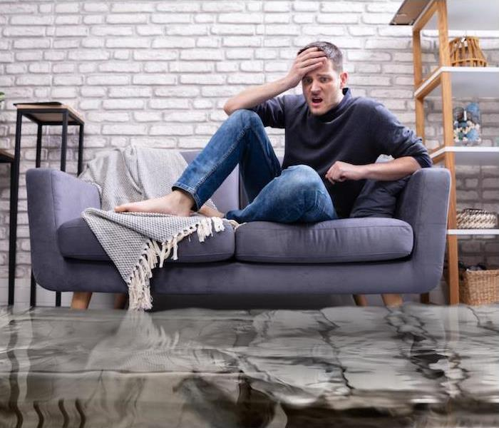 Upset Young Man Sitting On Sofa In The Living Room Flooded With Water