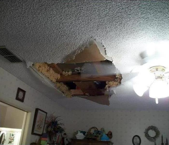 A large hole in a ceiling after a leak